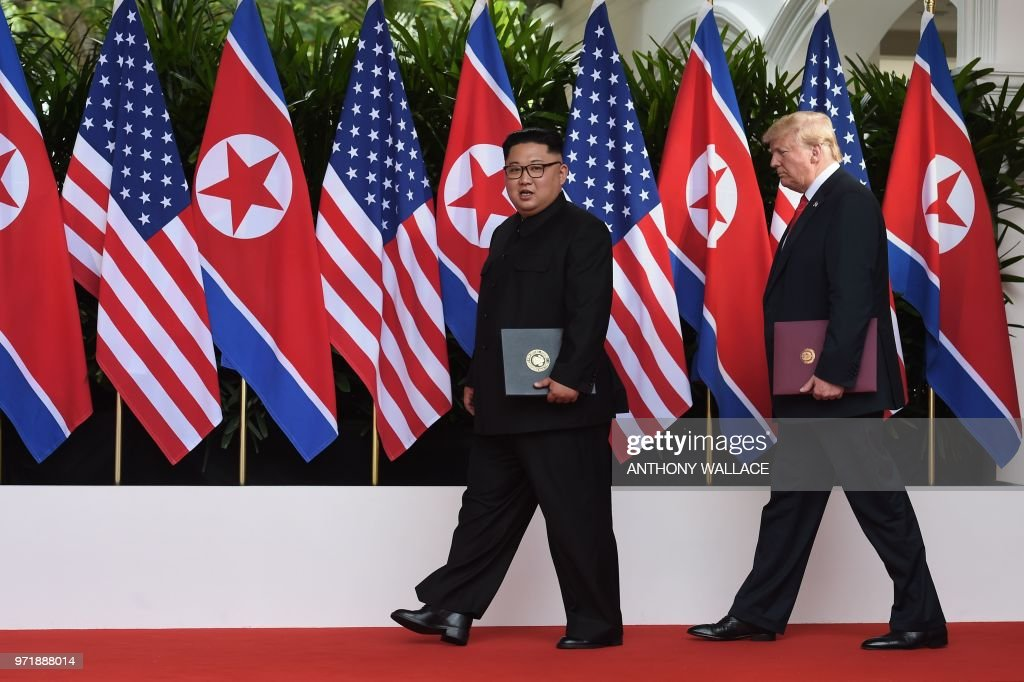 President Donald Trump (R) walks out with North Korea's leader Kim Jong Un (L) after taking part in a signing ceremony at the end of their historic US-North Korea summit, at the Capella Hotel on Sentosa island in Singapore on June 12, 2018. - Donald Trump and Kim Jong Un became on June 12 the first sitting US and North Korean leaders to meet, shake hands and negotiate to end a decades-old nuclear stand-off.