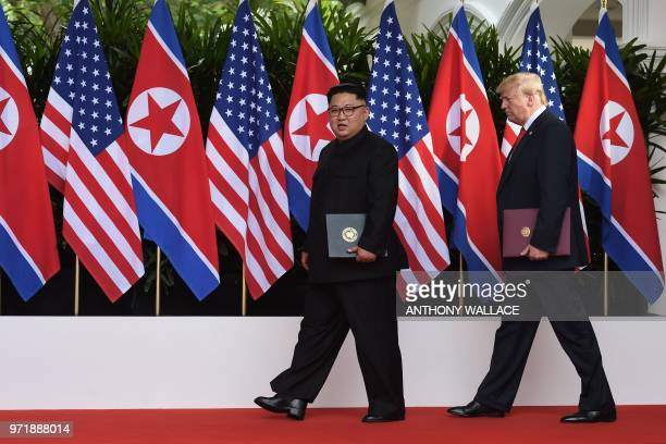 President Donald Trump walks out with North Korea's leader Kim Jong Un after taking part in a signing ceremony at the end of their historic US-North...