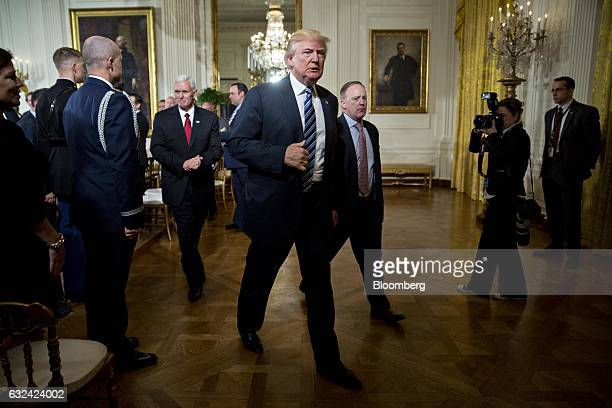US President Donald Trump walks out with US Vice President Mike Pence left and Sean Spicer White House press secretary right during a swearing in...