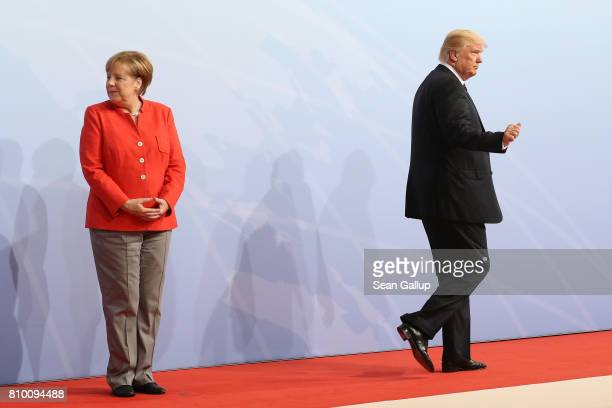 President Donald Trump walks past German Chancellor Angela Merkel after she greted him upon his arrival for the first day of the G20 economic summit...