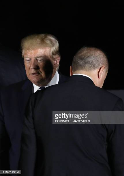 US President Donald Trump walks past Turkey's president Recep Tayyip Erdogan as they pose for a group photo during the G20 Summit in Osaka on June 28...