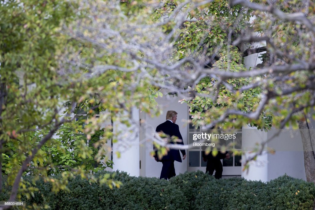 U.S. President Donald Trump walks through the Colonnade of the White House in Washington, D.C., U.S., on Monday, Oct. 30, 2017. Trump greeted costumed children during a traditional Halloween trick-or-treat at the White House, on the same day as Special Counsel Robert Mueller's investigation took a major turn as authorities charged three people -- a former campaign chief, his business associate and an ex-policy adviser -- with crimes including money laundering, lying to the FBI and conspiracy. Photographer: Andrew Harrer/Bloomberg via Getty Images