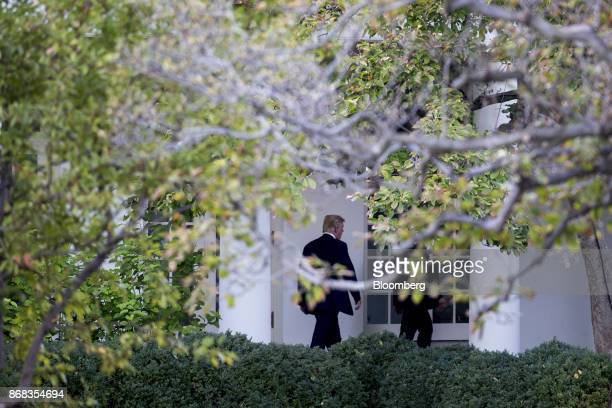 US President Donald Trump walks through the Colonnade of the White House in Washington DC US on Monday Oct 30 2017 Trump greeted costumed children...