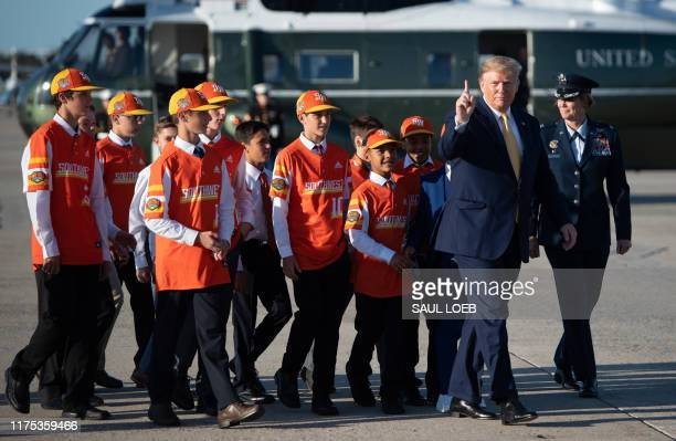 President Donald Trump walks to board Air Force One with members of the Little League World Championship baseball team, the Eastbank All Stars of...