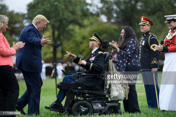 President Donald Trump walks to embrace Army Captain Luis Avila who sang God Bless American during a welcome ceremony for Chairman of the Joint...