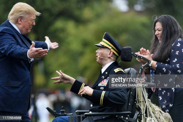 US President Donald Trump walks to embrace Army Captain Luis Avila who sang God Bless American during a welcome ceremony for Chairman of the Joint...