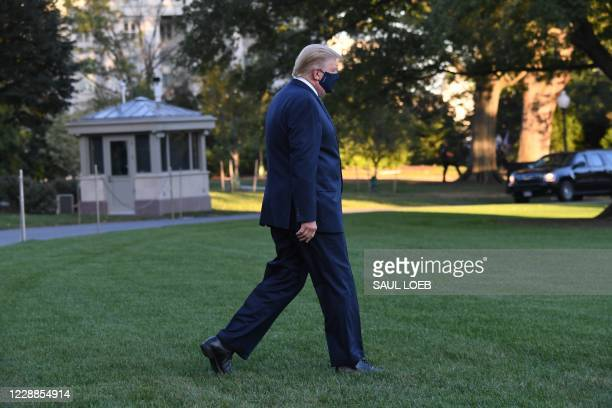 President Donald Trump walks to Marine One prior to departure from the South Lawn of the White House in Washington, DC, October 2 as he heads to...