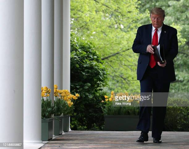 S President Donald Trump walks to the Rose Garden to attend the daily briefing of the White House Coronavirus Task Force at the White House April 14...