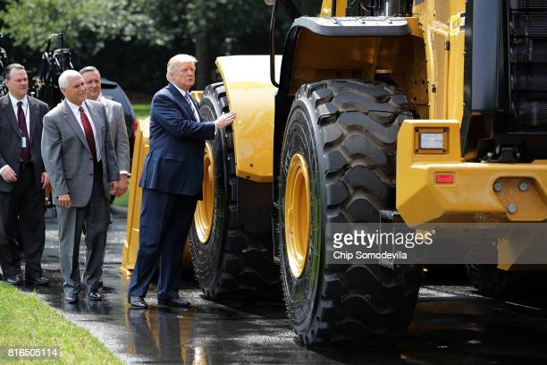 S President Donald Trump walks touches a wheel loader made by Caterpillar while touring a Made in America product showcase with Vice President Mike...