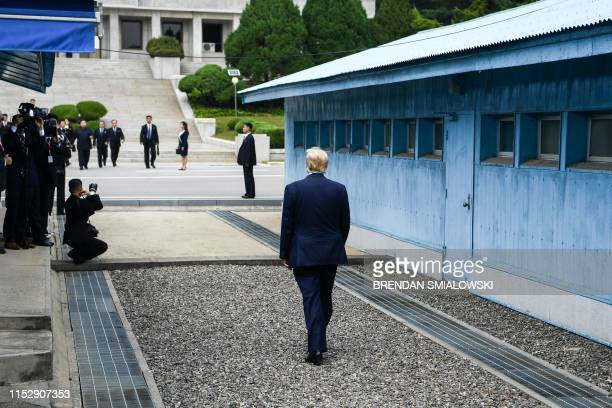 President Donald Trump walks towards the Military Demarcation Line that divides North and South Korea for a meeting with North Korea's leader Kim...