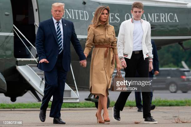 President Donald Trump walks with First Lady Melania Trump and their son Barron as they arrive at Morristown Municipal Airport in Morristown, New...