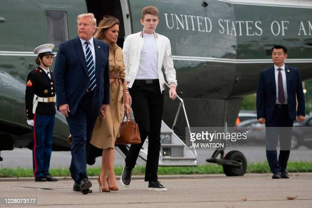 US President Donald Trump walks with First Lady Melania Trump and their son Barron as they arrive at Morristown Municipal Airport in Morristown New...