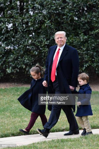 S President Donald Trump walks with his grandchildren Arabella Kushner and Joseph Kushner to board Marine One from the White House in Washington DC...