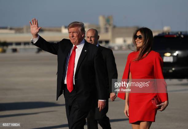 S President Donald Trump walks with his wife Melania Trump on the tarmac after he arrived on Air Force One at the Palm Beach International Airport...