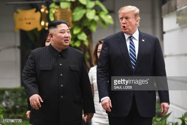 US President Donald Trump walks with North Korea's leader Kim Jong Un during a break in talks at the second USNorth Korea summit at the Sofitel...
