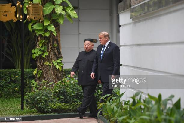 US President Donald Trump walks with North Korea's leader Kim Jong Un during a break in talks at the second USNorth Korea summit at the Sofitel...
