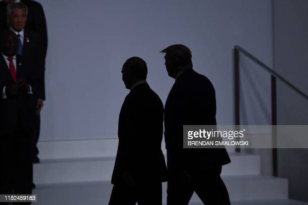 President Donald Trump walks with Russia's President Vladimir Putin before taking a family photo at the G20 Summit in Osaka on June 28, 2019.