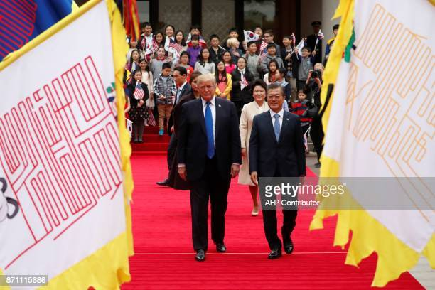US President Donald Trump walks with South Korea's President Moon Jaein during a welcoming ceremony at the presidential Blue House in Seoul on...
