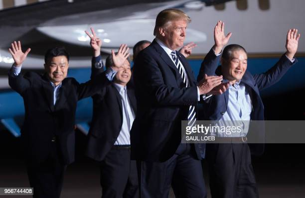 US President Donald Trump walks with US detainees Tony Kim Kim Haksong and Kim Dongchul upon their return after they were released by North Korea at...