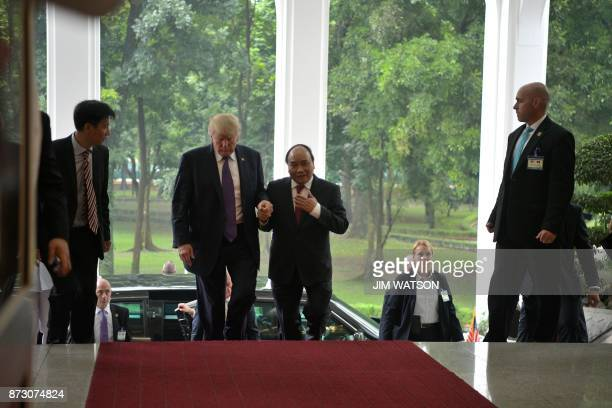 US President Donald Trump walks with Vietnamese Prime Minister Nguyen Xuan Phuc in Hanoi on November 12 2017 Trump arrived in the Vietnamese capital...