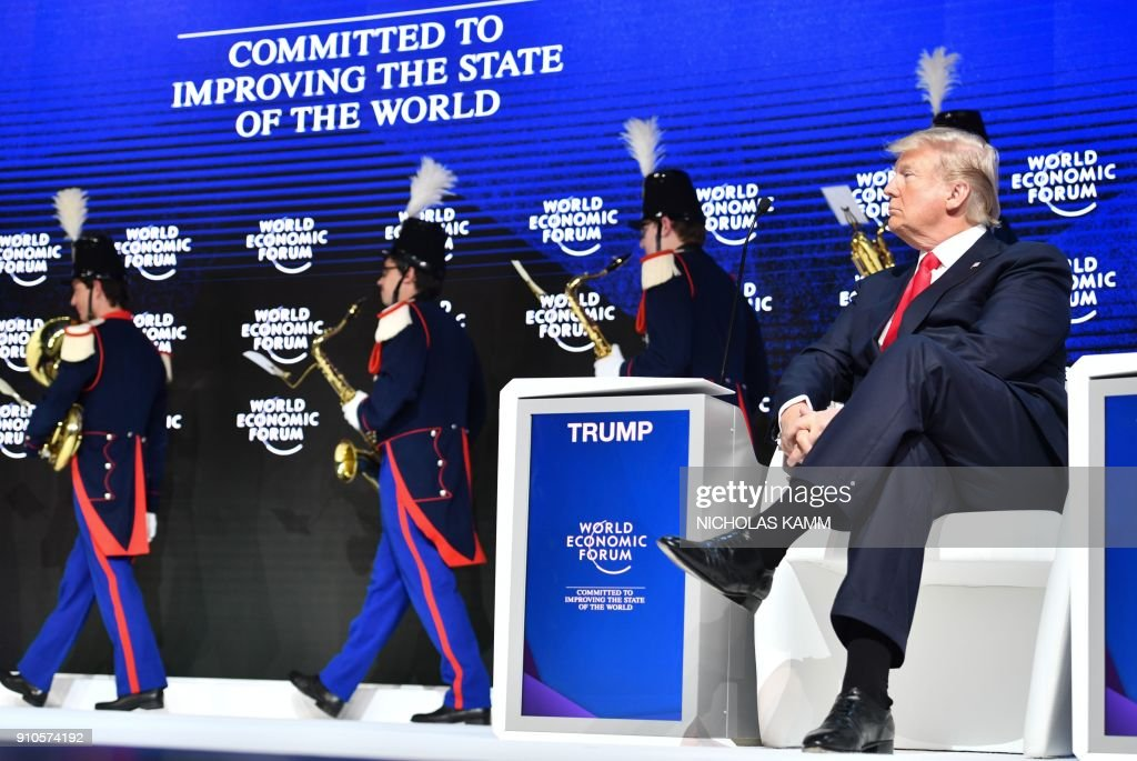 President Donald Trump watches a band leaving the stage after a ceremony and before delivering his speech during the World Economic Forum (WEF) annual meeting on January 26, 2018 in Davos, eastern Switzerland. / AFP PHOTO / Nicholas Kamm