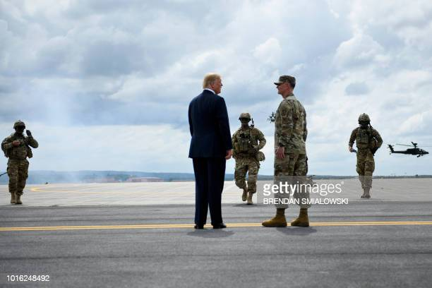 US President Donald Trump watches an air assault exercise with Army Major General Walter Piatt at Fort Drum New York on August 13 2018 Trump spoke at...
