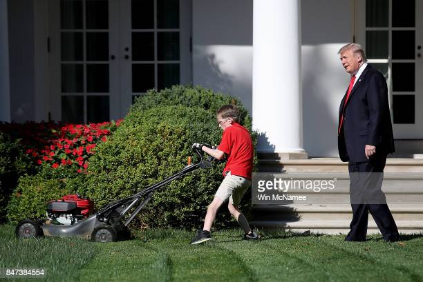S President Donald Trump watches as 11yearold Frank 'FX' Giaccio mows the grass in the Rose Garden of the White House September 15 2017 in Washington...