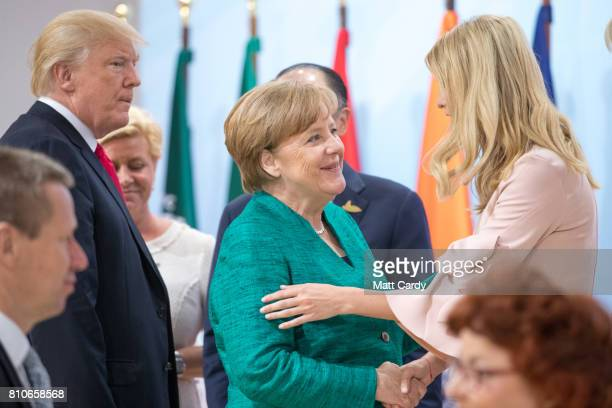 President Donald Trump watches as his daughter Ivanka Trump greets German Chancellor Angela Merkel at a panel discussion titled 'Launch Event Women's...