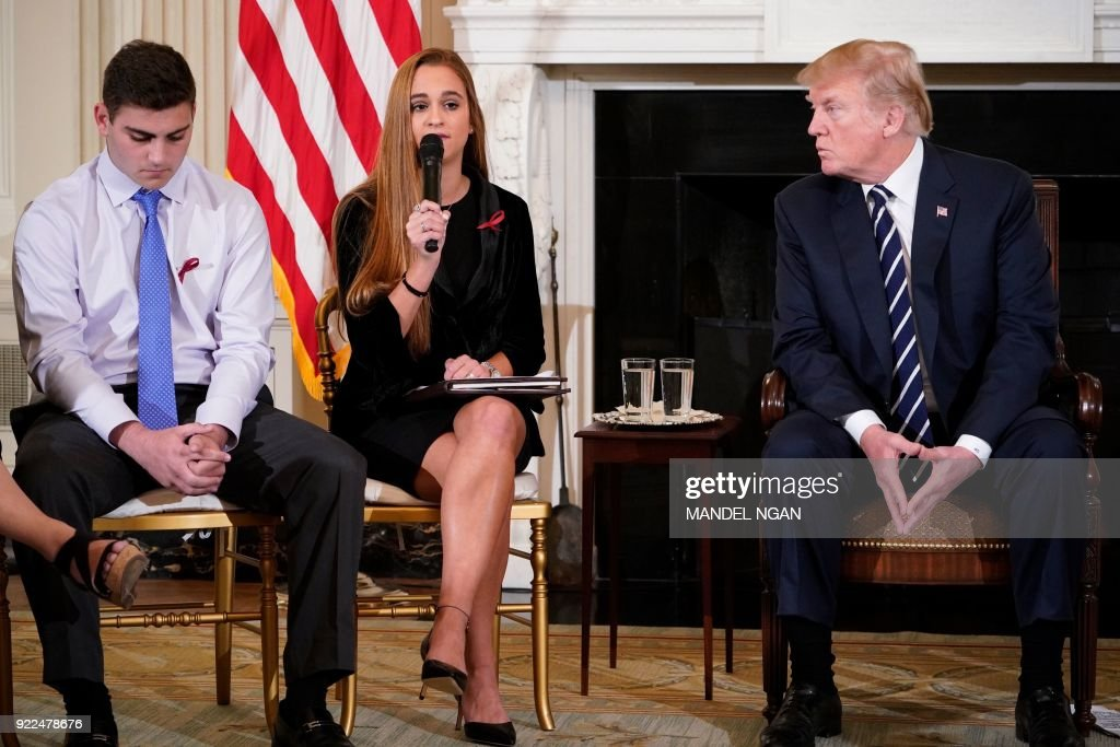 President Donald Trump (R) watches as Julia Cordover (C), Parkland student body president, speaks during a listening session on gun violence in the State Dining Room of the White House on February 21, 2018. At right is Nicole Hockley of Sandy Hook Promise. /