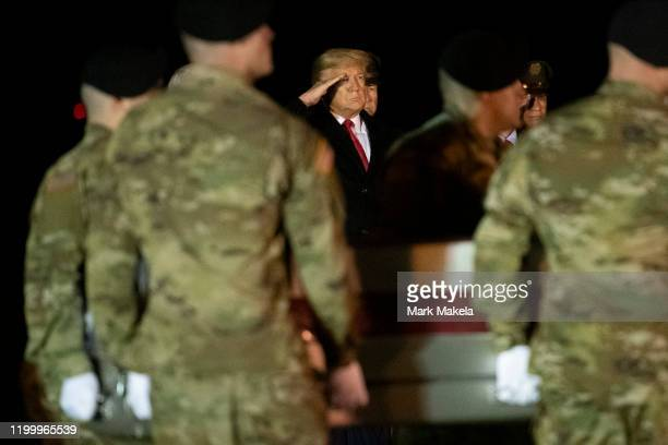 President Donald Trump watches as military personnel carry a transfer case for fallen service member, U.S. Army Sgt. 1st Class Javier J. Gutierrez...