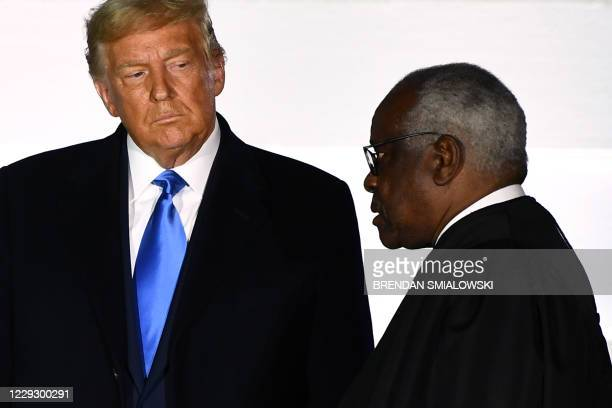 President Donald Trump watches as Supreme Court Associate Justice Clarence Thomas swears in Judge Amy Coney Barrett as a US Supreme Court Associate...