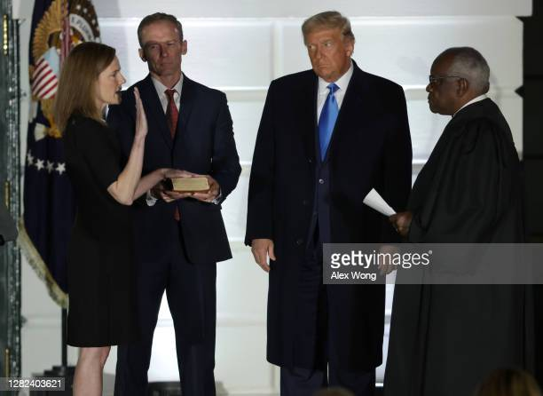 President Donald Trump watches as U.S. Supreme Court Associate Justice Amy Coney Barrett is sworn in by Supreme Court Associate Justice Clarence...