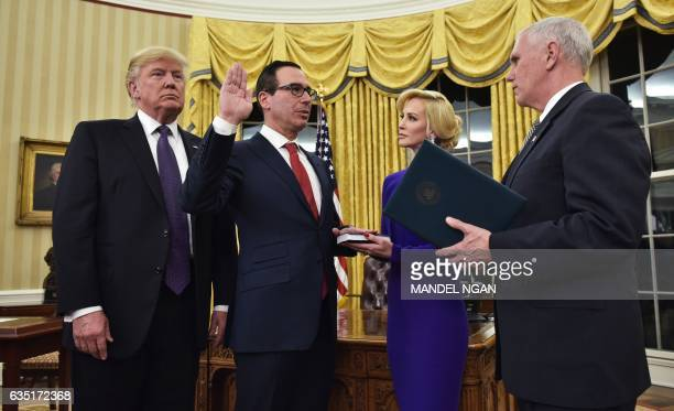 President Donald Trump watches as US Vice President Mike Pence administers the oath of office to Treasury Secretary Steven Mnuchin watched by...
