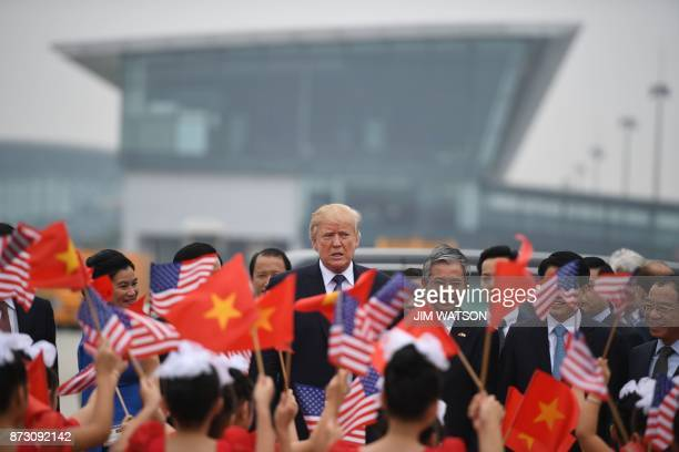 US President Donald Trump watches as young girls wave US and Vietnamese national flags before boarding Air Force One to depart to the Philippines at...