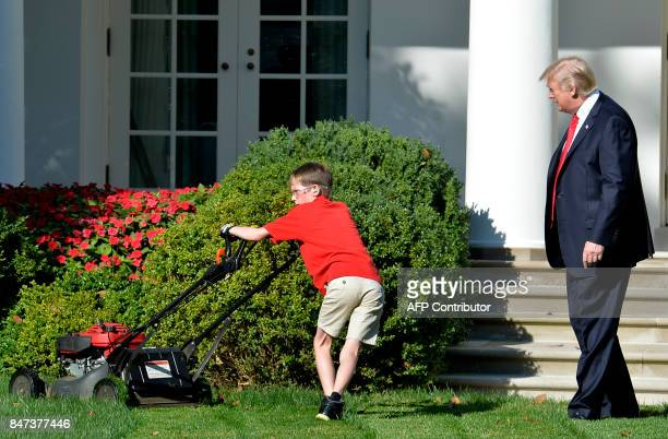 TOPSHOT President Donald Trump watches Frank Giaccio of Falls Church Virginia as he mows the lawn in the Rose Garden of the White House on September...