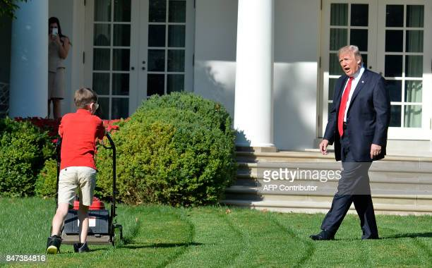 US President Donald Trump watches Frank Giaccio of Falls Church Virginia as he mows the lawn in the Rose Garden of the White House on September 15 in...