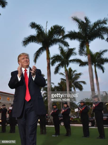 US President Donald Trump watches the Palm Beach Central High School marching band which greeted him as he arrived to watch the Super Bowl at Trump...