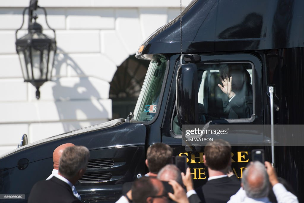 US President Donald Trump (C) waves after closing the door as he sits in the drivers seat of a semi-truck while welcoming truckers and CEOs to the White House in Washington, DC, March 23, 2017, to discuss healthcare. /