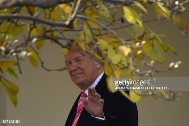 US President Donald Trump waves after he pardoned the turkey Drumstick during the turkey pardoning ceremony at the White House in Washington DC on...