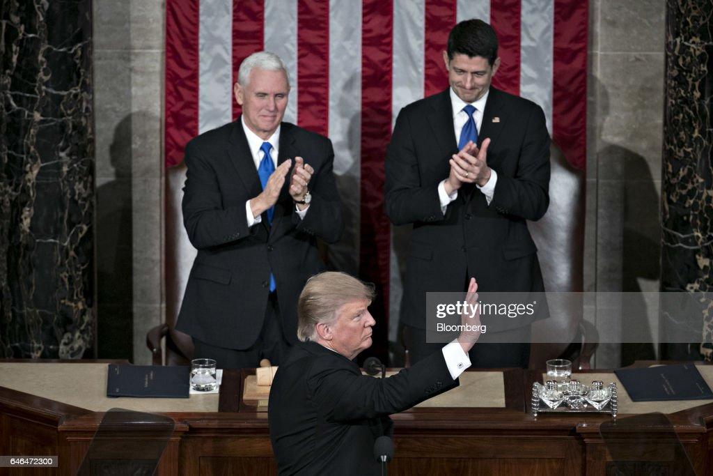 U.S. President Donald Trump waves after speaking as U.S. Vice President Mike Pence, left, and U.S. House Speaker Paul Ryan, a Republican from Wisconsin, applaud during a joint session of Congress in Washington, D.C., U.S., on Tuesday, Feb. 28, 2017. Trump will press Congress to carry out his priorities for replacing Obamacare, jump-starting the economy and bolstering the nations defenses in an address eagerly awaited by lawmakers, investors and the public who want greater clarity on his policy agenda. Photographer: Andrew Harrer/Bloomberg via Getty Images