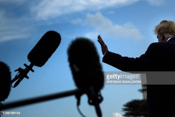 US President Donald Trump waves after speaking to the press as he departs the White House in Washington DC on July 17 2019 Trump travels to...