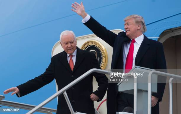 US President Donald Trump waves alongside US Senator Orrin Hatch Republican of Utah as they disembark from Air Force One upon arrival at Salt Lake...