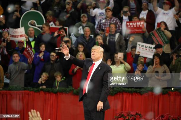 S President Donald Trump waves as fake snow falls as he ends a rally at the Pensacola Bay Center on December 8 2017 in Pensacola Florida Mr Trump...