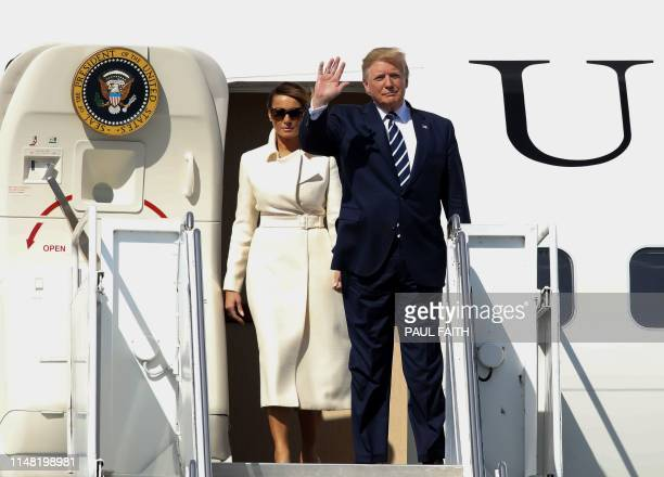 US President Donald Trump waves as he and First Lady Melania Trump disembark Air Force One upon arrival at Shannon Airport in Shannon County Clare...