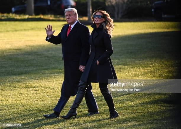 President Donald Trump waves as he and First Lady Melania Trump walk towards Marine One on the South Lawn of the White House on their way to Joint...