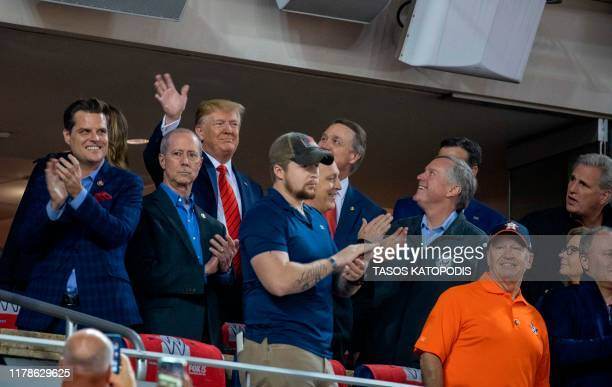 US President Donald Trump waves as he attends Game 5 of the World Series between the Washington Nationals and Houston Astros at Nationals Park in...