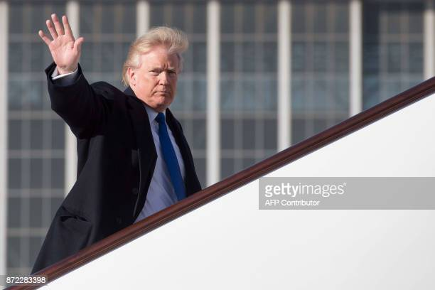 US President Donald Trump waves as he boards Air Force One before flying to Vietnam to attend the annual Asia Pacific Economic Cooperation forum at...