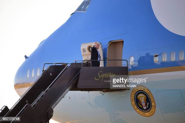 US President Donald Trump waves as he boards Air Force One before departing from St Louis Lambert International Airport in St Louis Missouri on March...