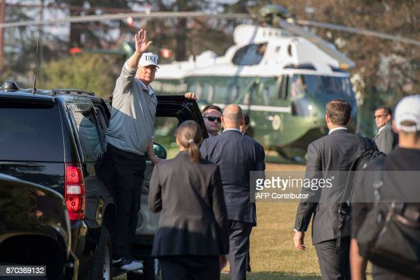 US President Donald Trump waves as he exits his vehicle after playing a round of golf with Japanese Prime Minister Shinzo Abe at the Kasumigaseki...