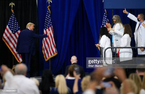 S President Donald Trump waves as he makes his way off stage after signing an executive order following his remarks on his healthcare policies on...